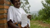 A woman smiles as she holds a title for her land